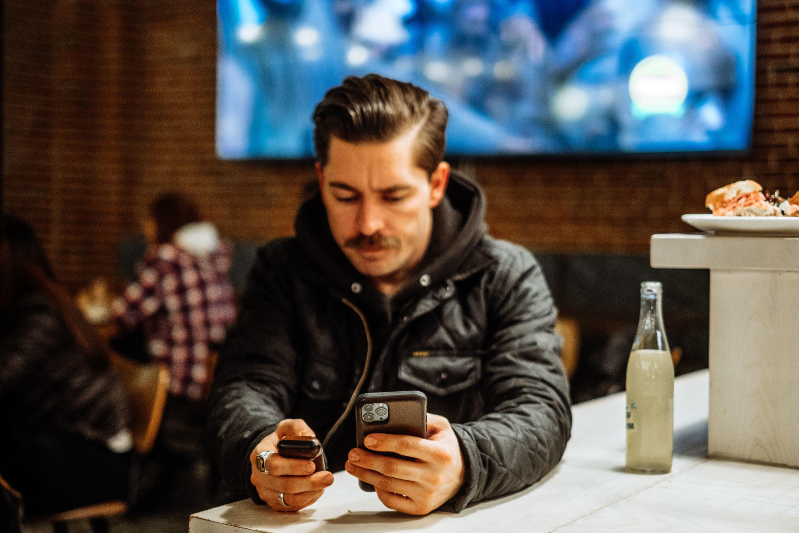 Man Using AudioFetch App in Sports Bar