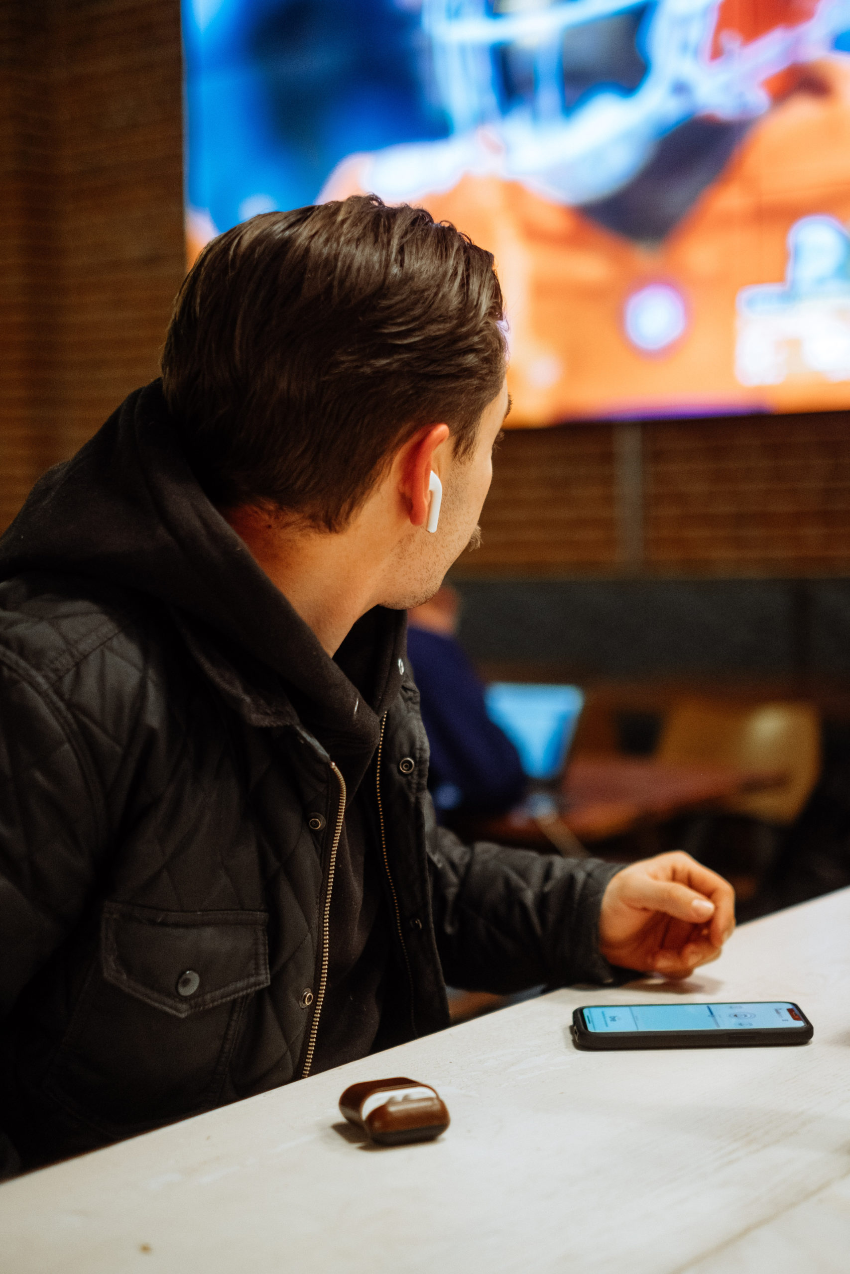 Man Using AudioFetch App Watching Football in Sports Bar