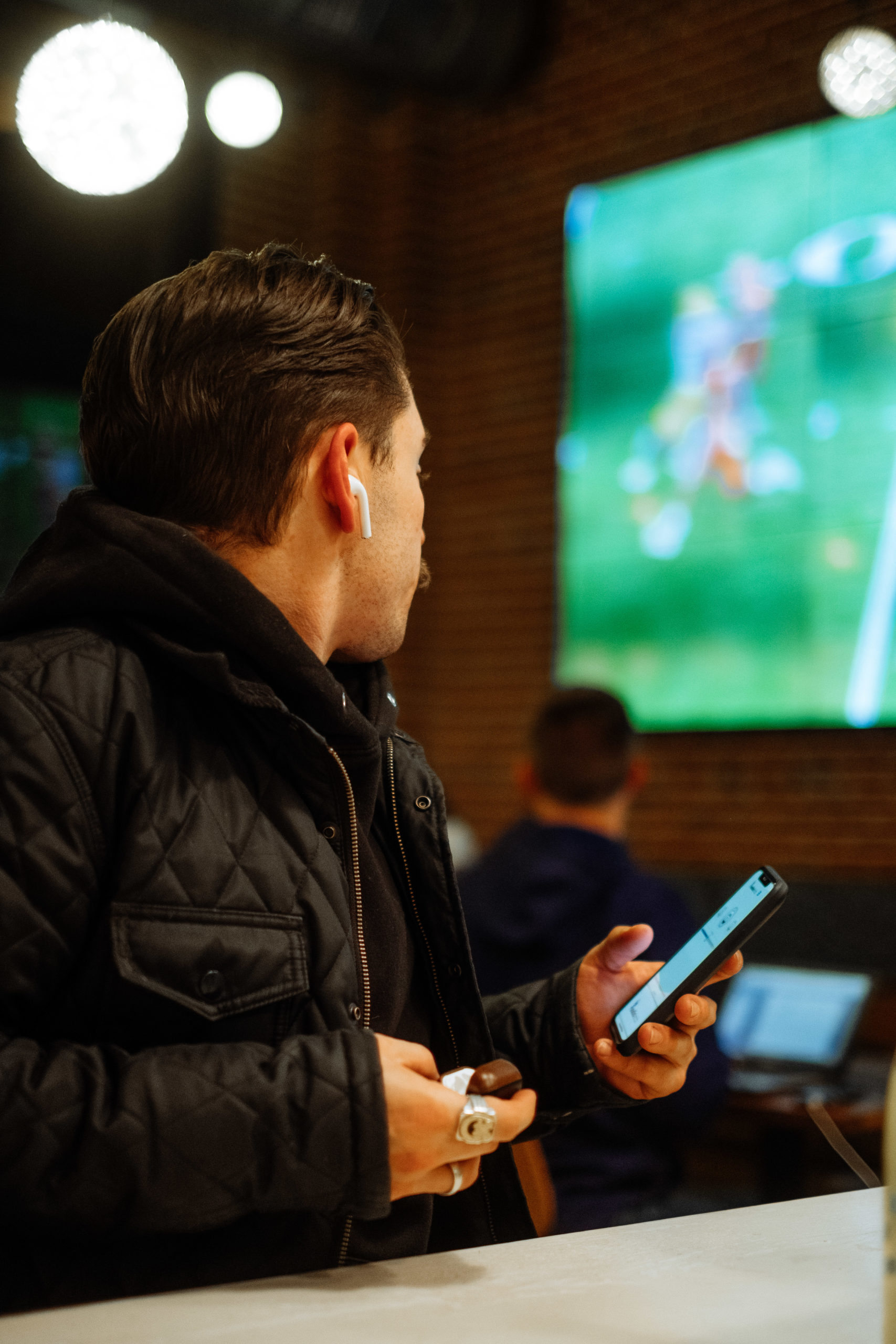 Man Using AudioFetch App Watching Game in Sports Bar