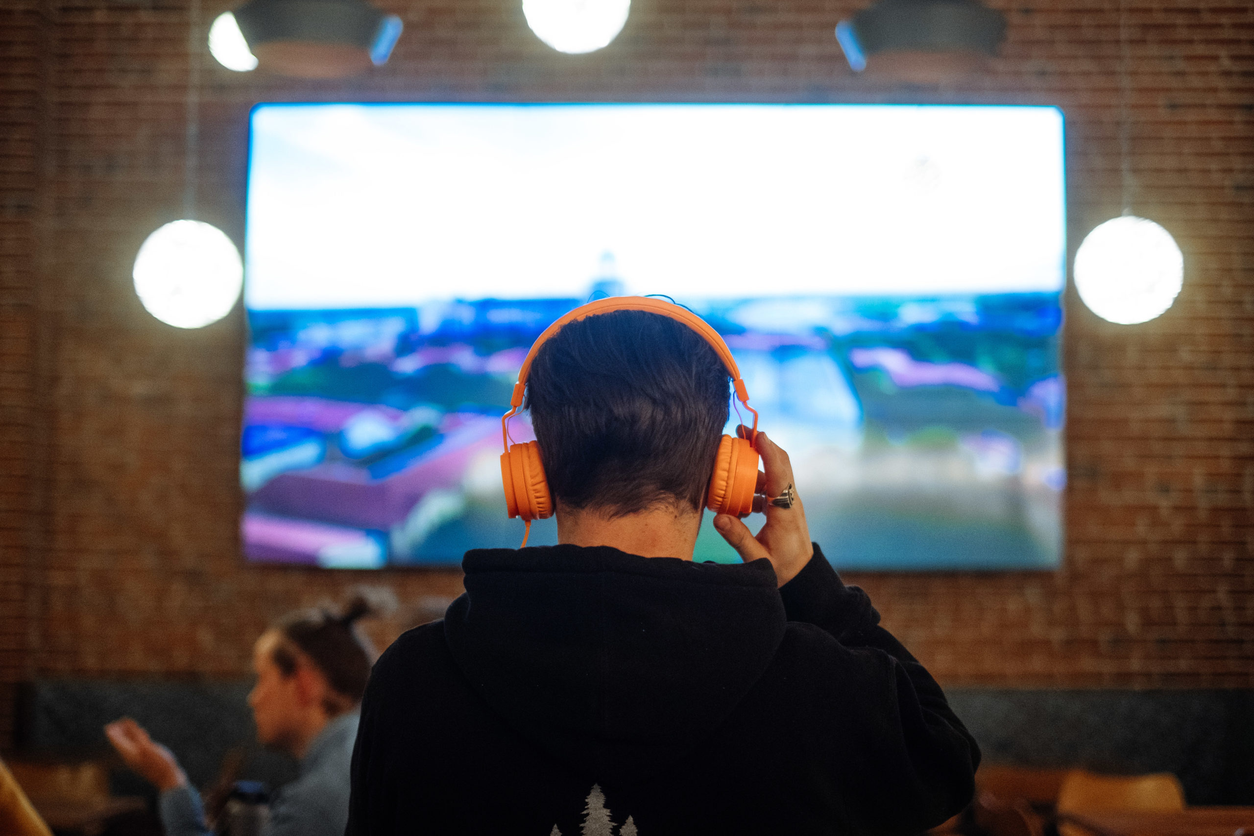 Man with Headphones Watching TV in Sports Bar