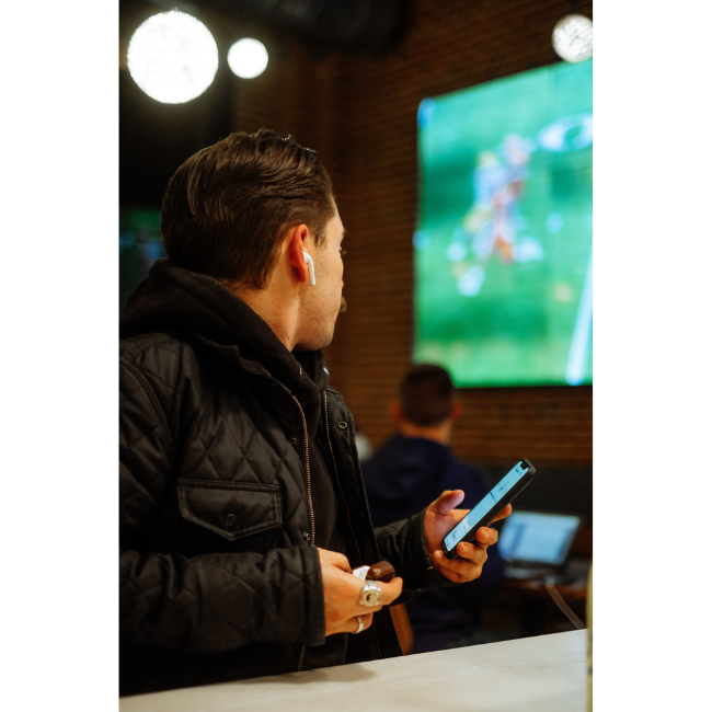 Man Using AudioFetch App at Sports Bar