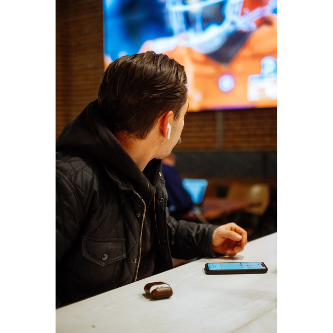 Man Using AudioFetch App - Hear TV at Sports Bar